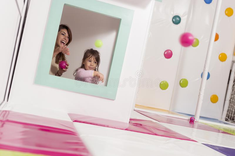 Throwing balls. Mother and daughter playing in a playroom, hiding in a small wooden house, throwing balls through the window. Focus on the mother stock photography