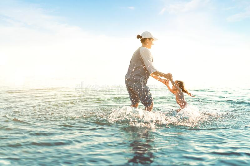 Mother and daughter playing at the sea. Active summer leisure on the vacation. Mom and child having fun on the water. Holding her children on the hands anв stock photos