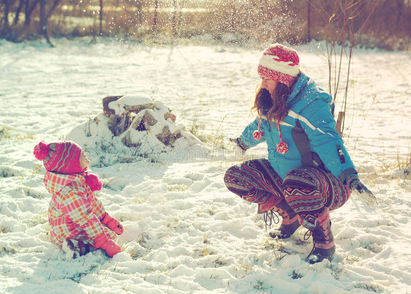 Mother and daughter playing in the snow. Happy mother and her daughter playing in the snow royalty free stock images