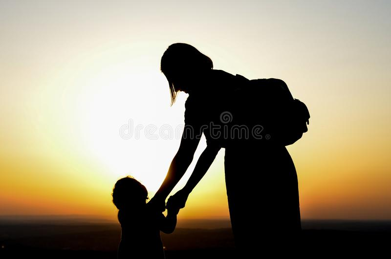 Mother and daughter playing during  sunset stock photos