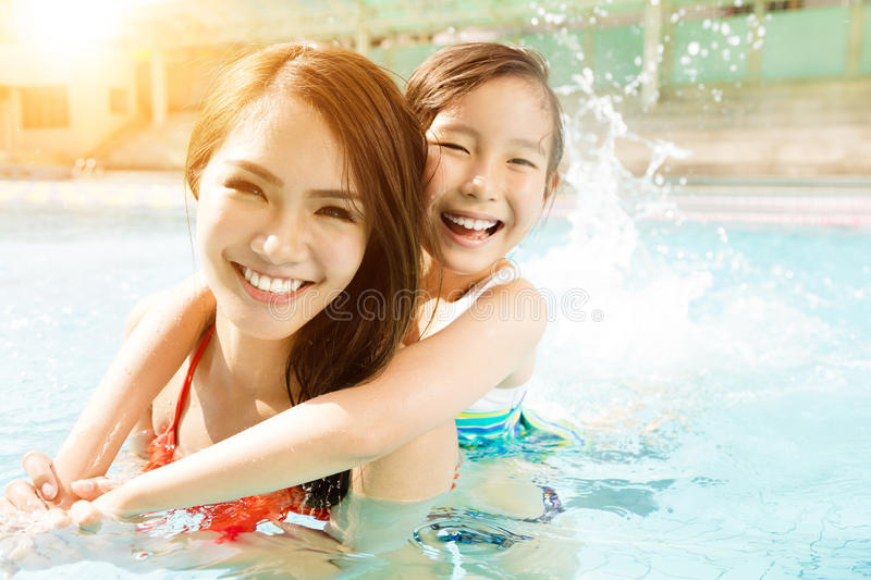 Mother and daughter playing in swimming pool royalty free stock photography