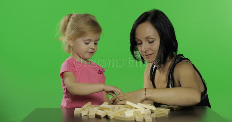 Mother and daughter plays the jenga. Child making a tower from wooden blocks royalty free stock photography
