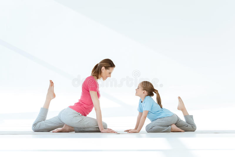 Mother and daughter practicing pigeon yoga pose on mats and looking at each other stock image
