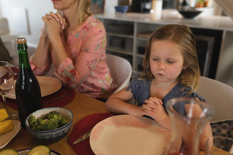 Mother and daughter praying together before having meal royalty free stock image