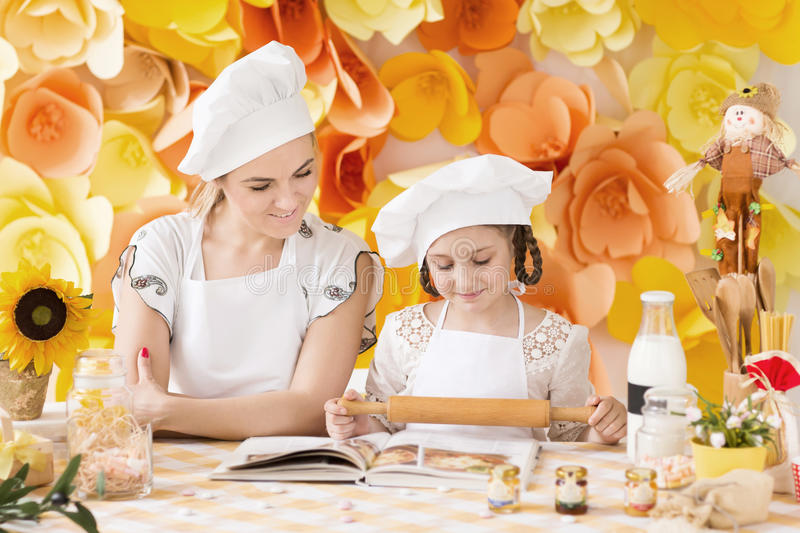 Mother and daughter preparing dinner in the kitchen. Mother and daughter playing in the chefs and cooks dinner in the kitchen stock photos