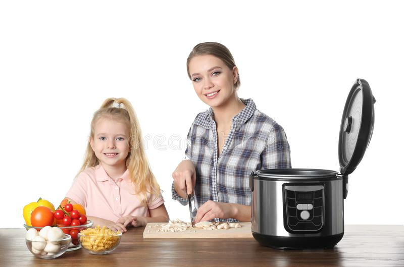 Mother and daughter preparing food with multi cooker at table against white background royalty free stock photography