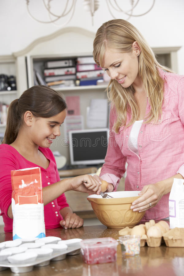 Mother And Daughter Preparing Ingredients To Bake Cakes In Kitchen royalty free stock photography