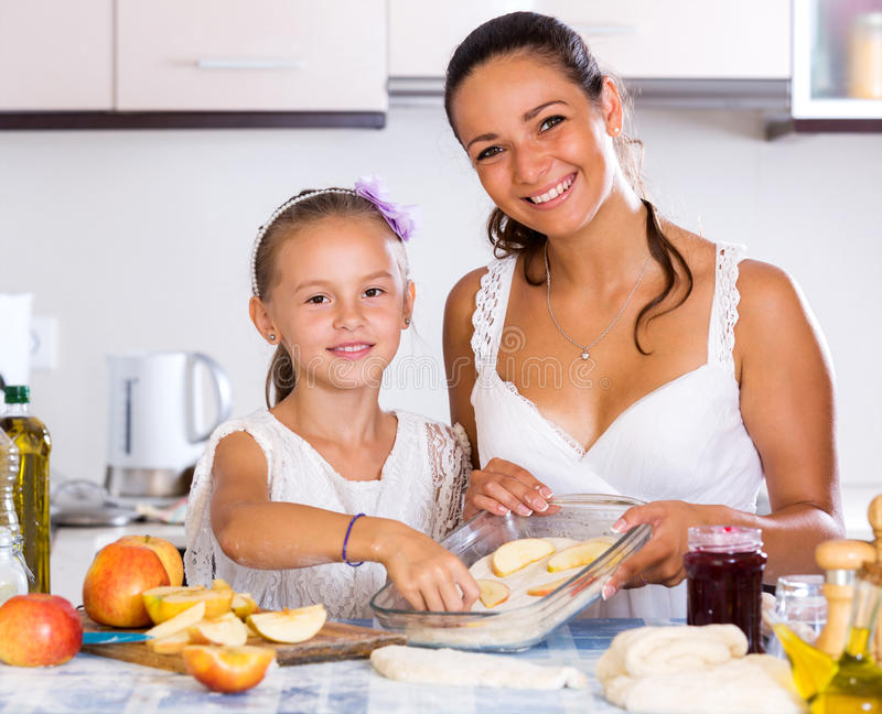 Mother and daughter preparing pie. Happy little daughter helping mom to make apple cake at home. Focus on the girl royalty free stock images