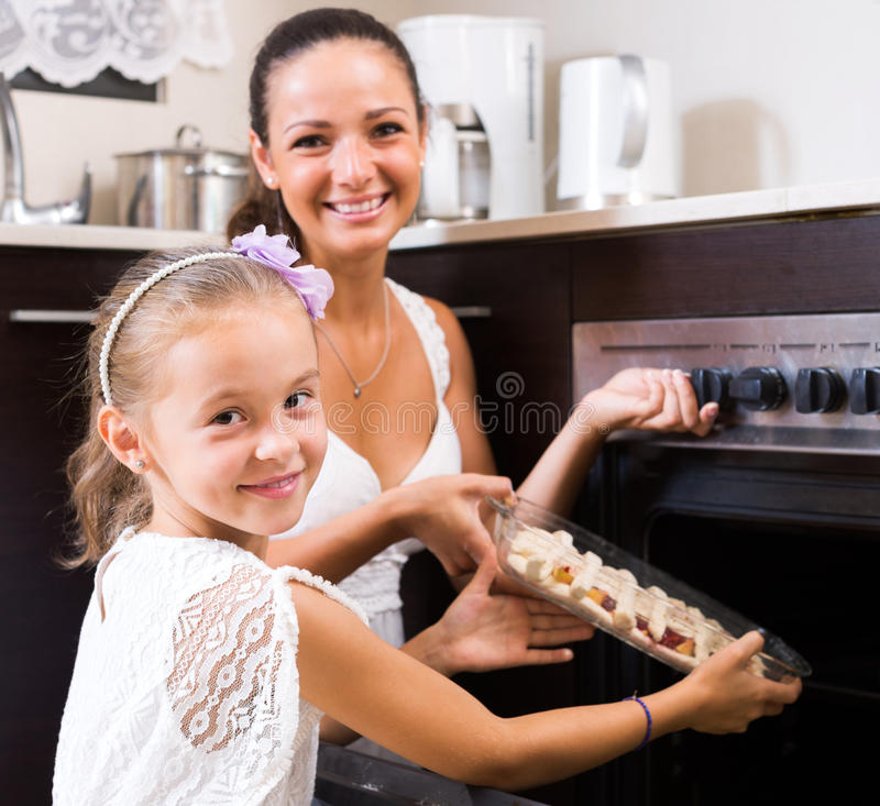 Mother and daughter preparing pie. Little girl helping mom to make apple cake at home. Focus on the girl royalty free stock photo