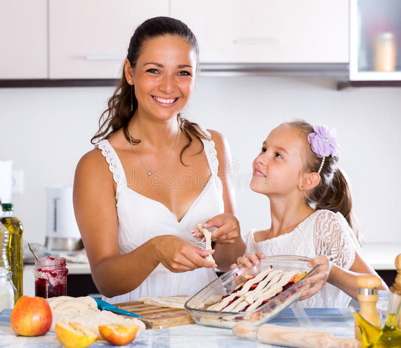 Mother and daughter preparing pie. Positive little girl helping mom to make apple cake at home. Focus on the woman royalty free stock photos