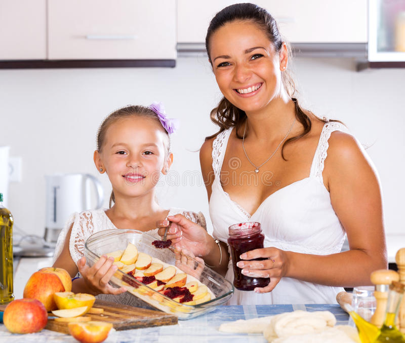 Mother and daughter preparing pie. Positive little daughter helping mom to make apple cake at home. Focus on the girl royalty free stock images