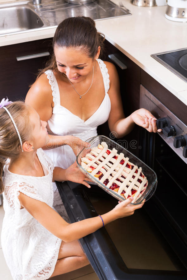 Mother and daughter preparing pie. Smiling little girl helping mom to make apple cake at home royalty free stock images