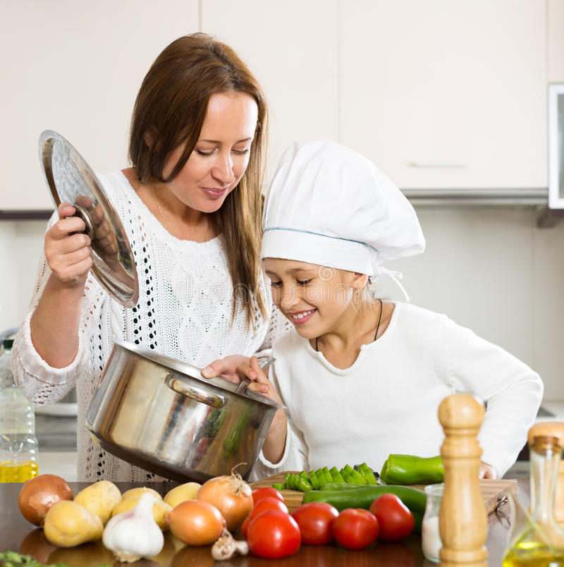 Happy Girl Kitchen: Mother And Daughter Preparing Soup Stock Photo