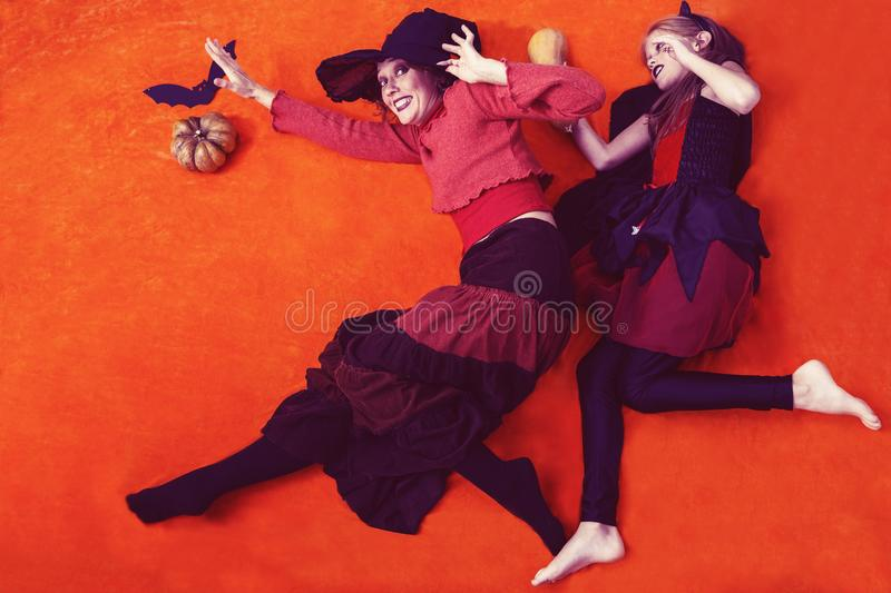 Mother and daughter pretend to be witches. Cheerful halloween in a family - mother and daughter in a costumes and makeup for Halloween, pretend to be witches,run royalty free stock photography