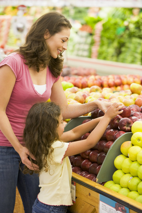 Mother and daughter in produce section stock photography