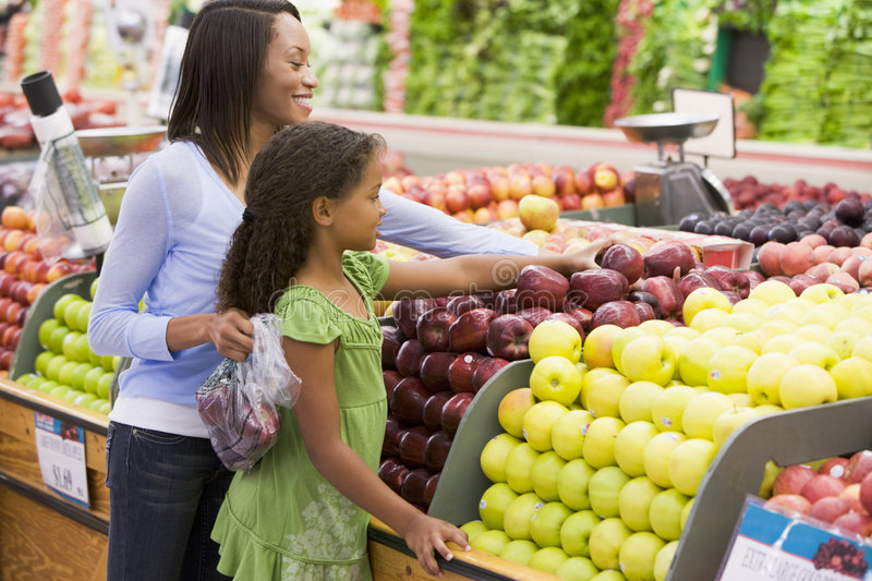 Mother and daughter in produce section royalty free stock photos