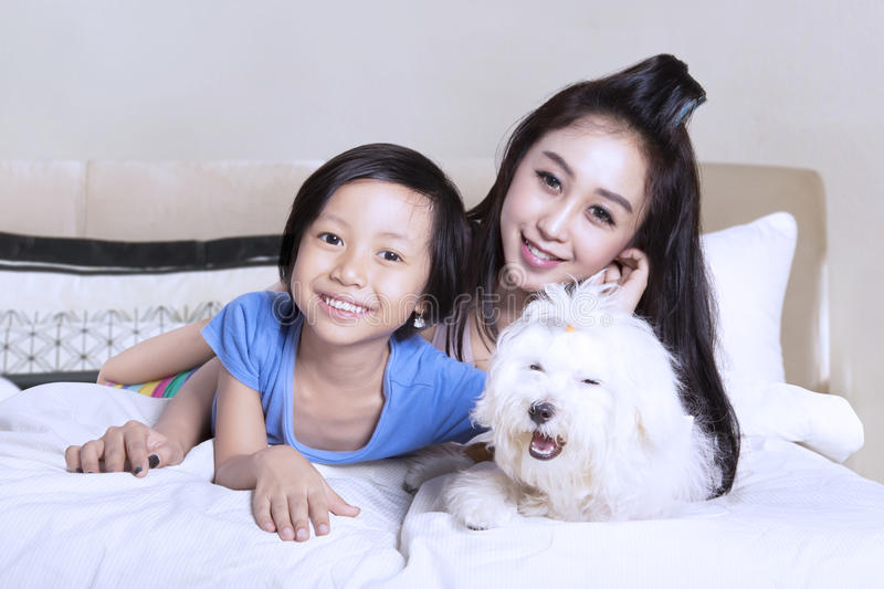 Mother and daughter with puppy on bedroom stock image