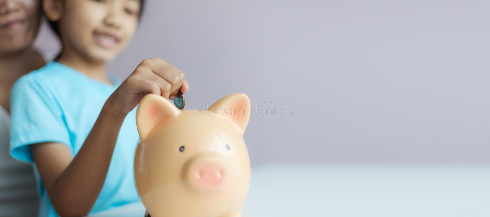 Mother and daughter putting coin into the piggy bank for money saving for the future concept select focus shallow depth of field. With copy space, family, girl royalty free stock photos