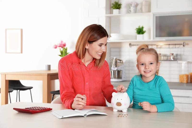 Mother and daughter putting coin into piggy bank at table indoors royalty free stock photography