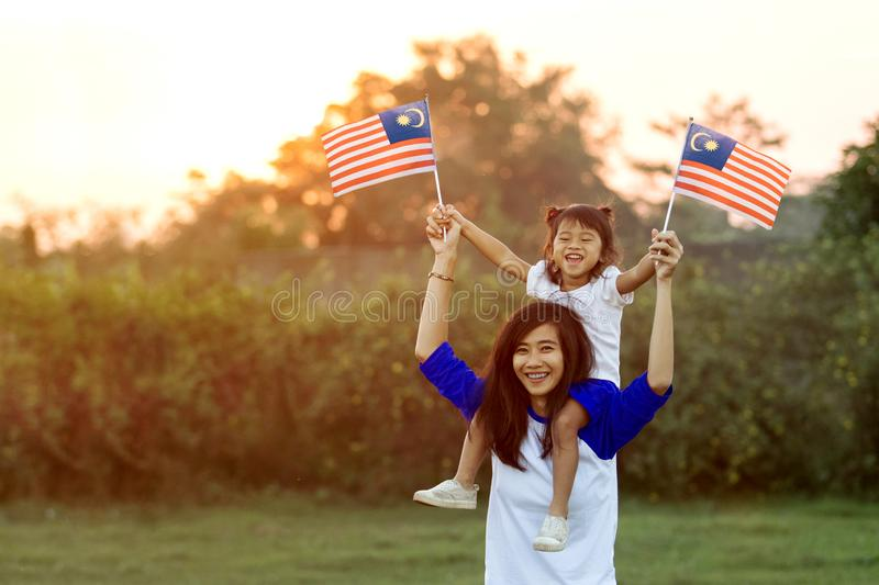 Mother and daughter raising flag of malaysia. Beautiful young mother with her daughter celebrating malaysia independence day by raising flag under the sunset sky royalty free stock image