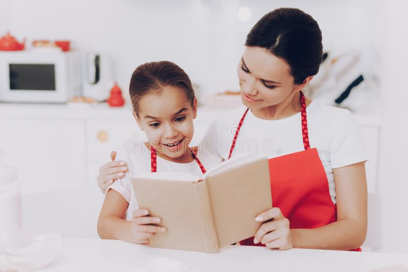 Mother and Daughter Read Book. Cake for Family. royalty free stock photography