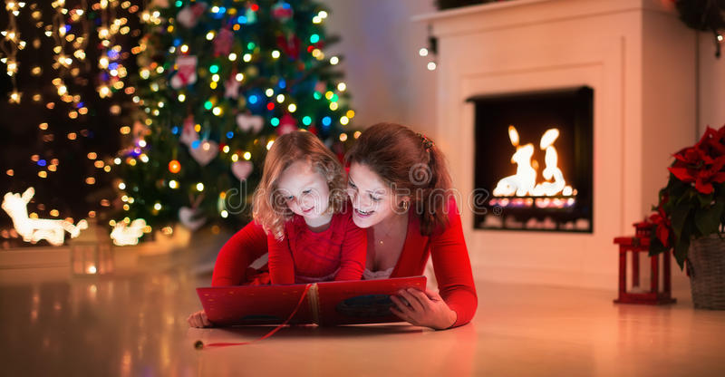 Mother and daughter read a book at fireplace on Christmas eve. stock photo