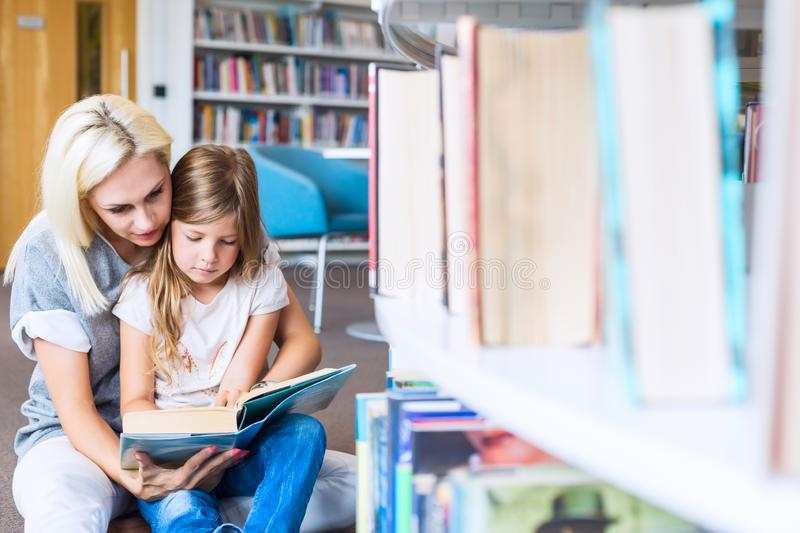 Mother with daughter read book together in library. Happy family, preschool concept. Parent educating children stock images
