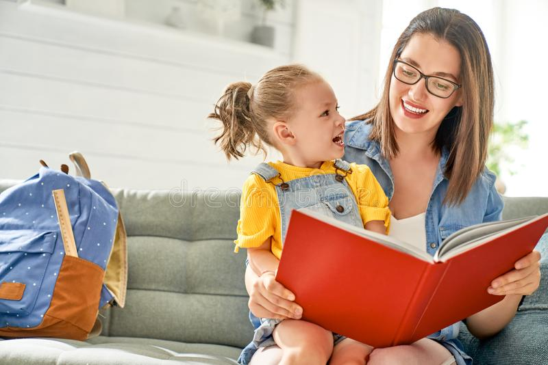 Mother and daughter are reading a book stock images