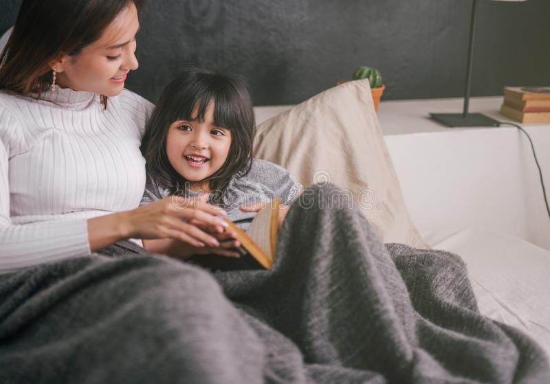 Mother and daughter reading book at home in the bedroom stock image