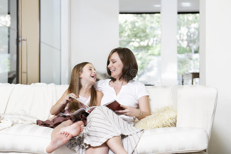 Mother And Daughter Reading Book In Living Room stock photography
