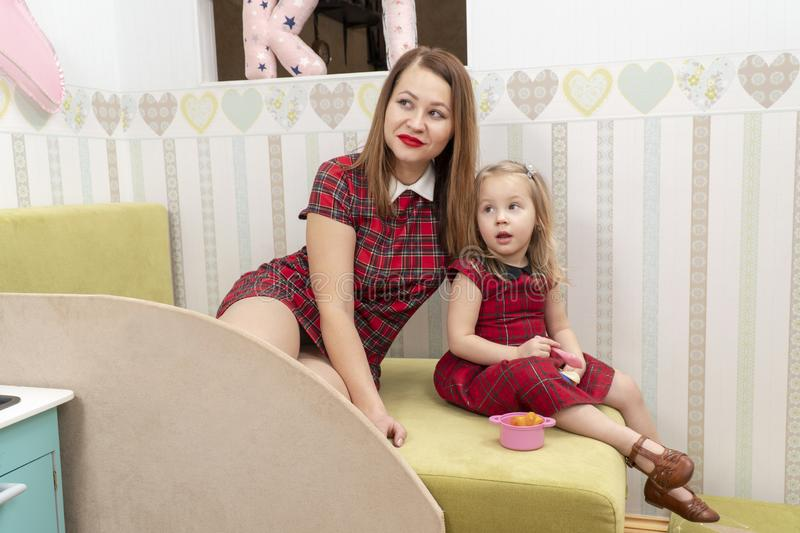 Mother and daughter in red dresses. Portrait of mother and daughter in red dresses on the baby bed in the children room stock photo