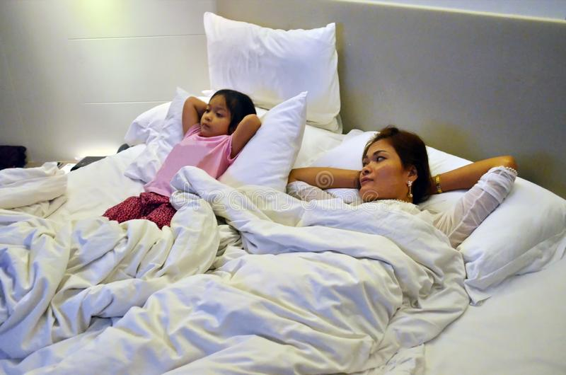 Mother and daughter relax in bed watching TV. stock images