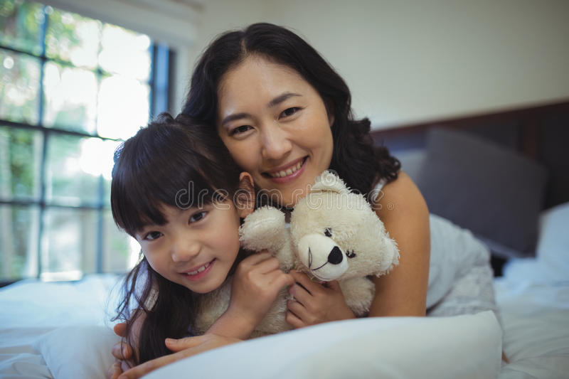 Mother and daughter relaxing on bed in bed room royalty free stock photography