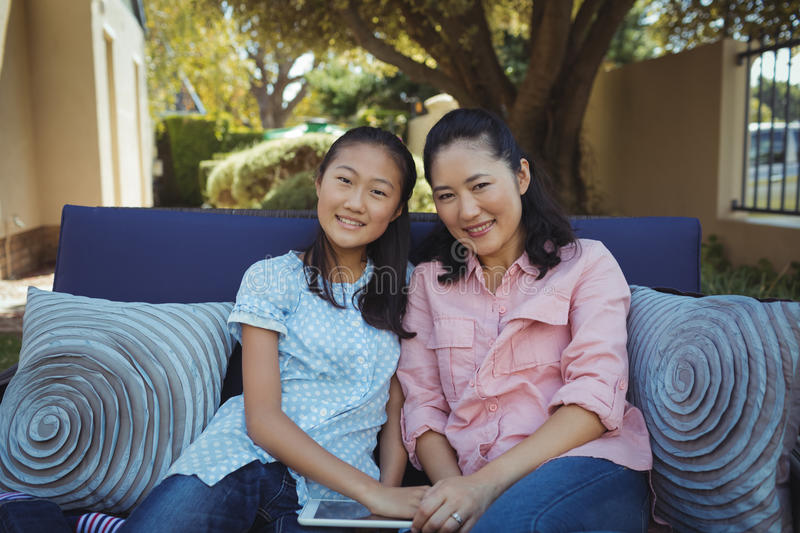 Mother and daughter relaxing on couch outside home royalty free stock image