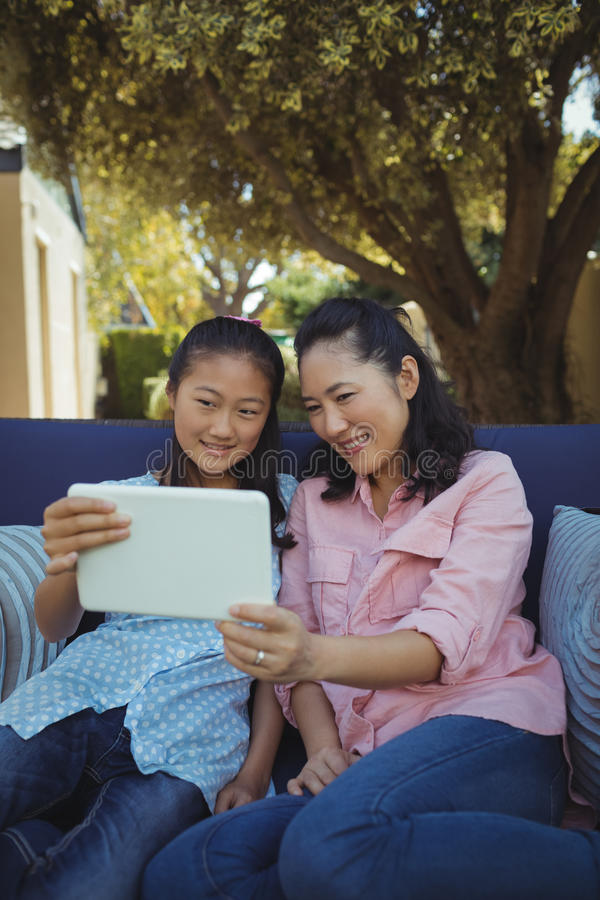Mother and daughter relaxing on couch and using digital tablet stock photos
