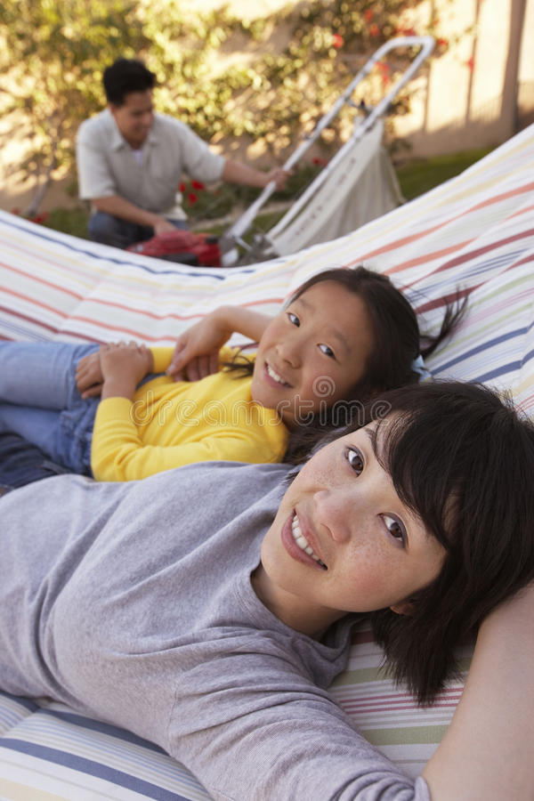 Mother And Daughter Relaxing On Hammock royalty free stock photos