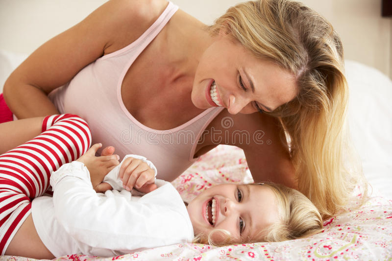 Mother And Daughter Relaxing Together In Bed royalty free stock photography
