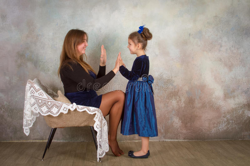 Mother And Daughter Relaxing Together In Chair stock photo