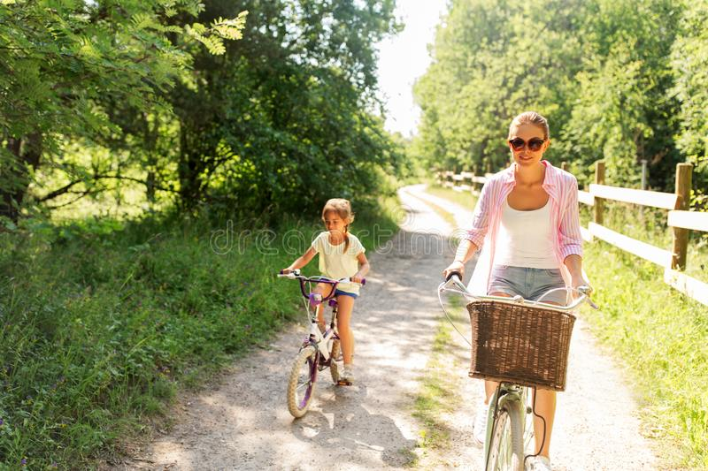 Mother and daughter riding bikes in summer park stock photo