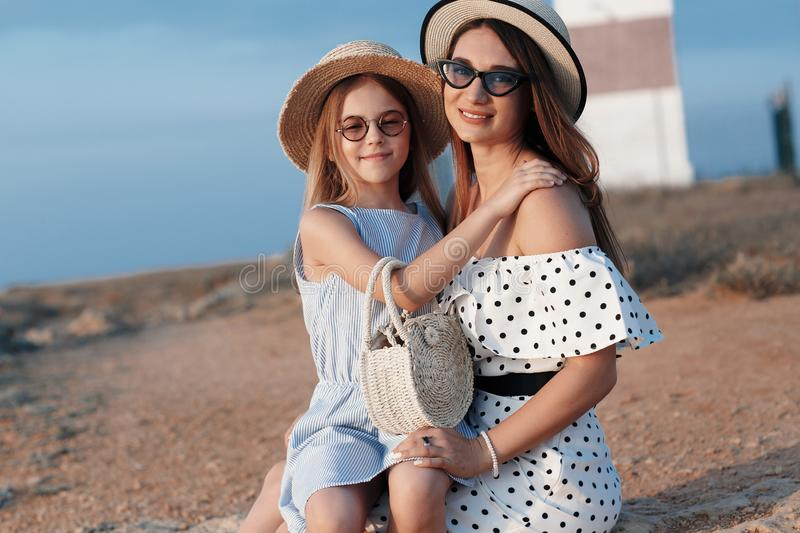 Mother and daughter on the rocky shore of the ocean in late spring stock image