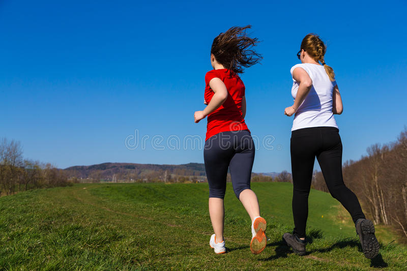 Mother and daughter running. Active family - mother with daughter running stock photo