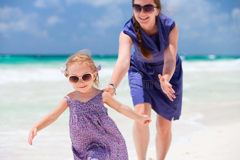 Mother and daughter running at beach stock photography