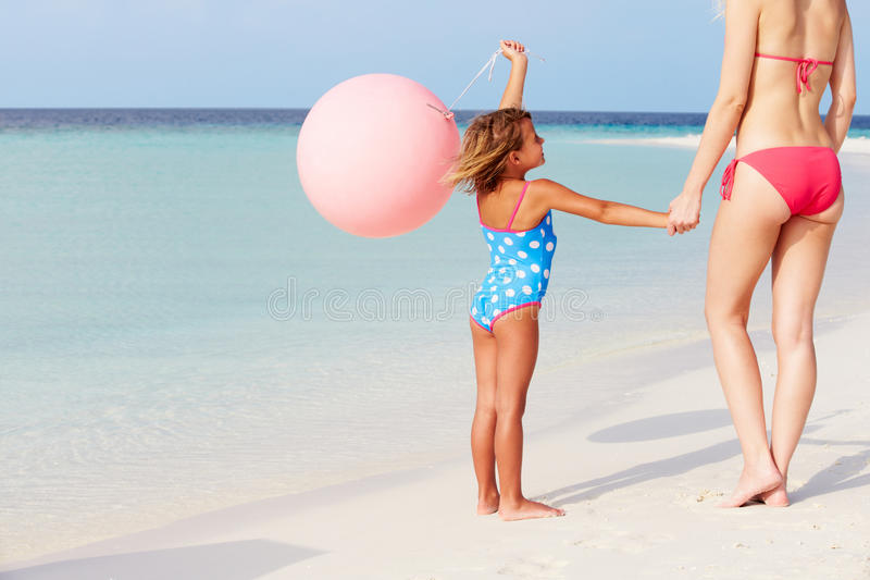 Mother And Daughter Running On Beautiful Beach With Balloon. Having Fun royalty free stock images