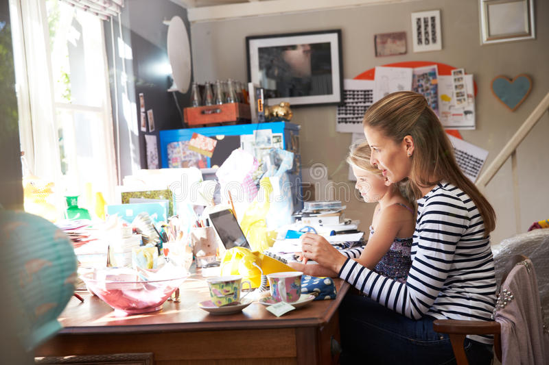 Mother With Daughter Running Small Business From Home Office royalty free stock photos