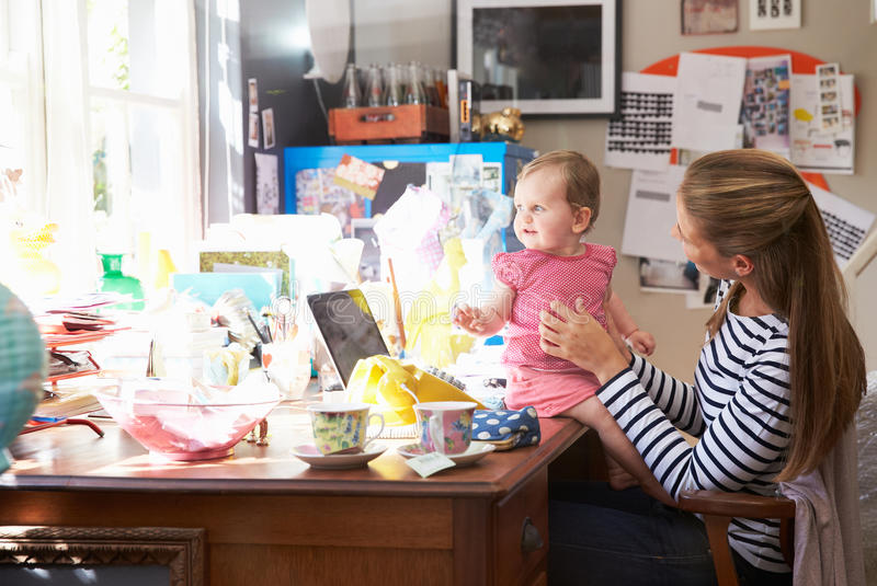 Mother With Daughter Running Small Business From Home Office stock image