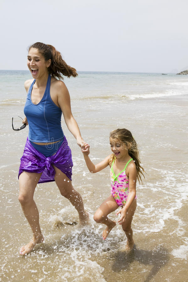 Mother and Daughter Running Through Water on Beach royalty free stock images