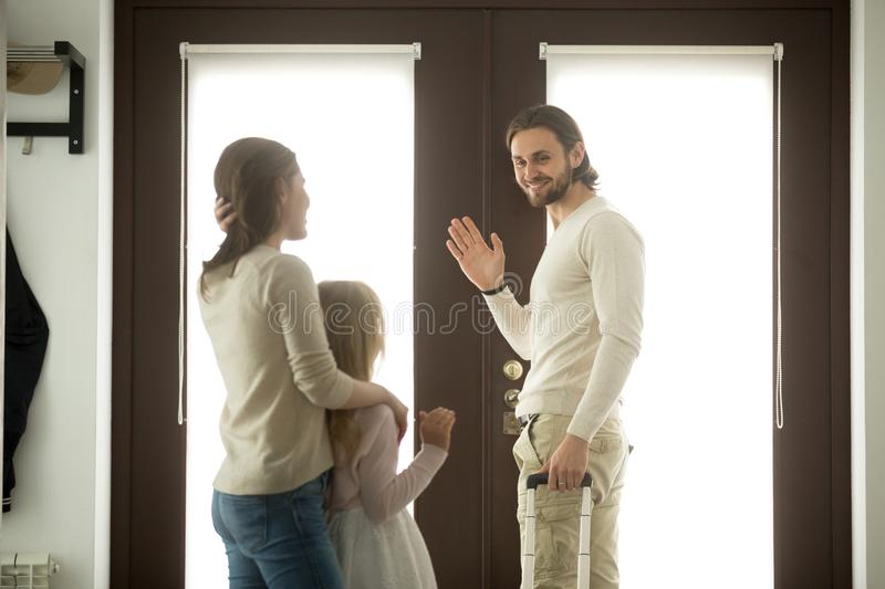 Mother and daughter seeing off father leaving, waving hands good stock photo