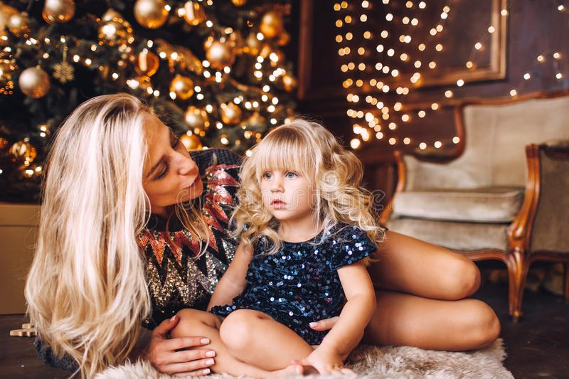 Mother and daughter in shiny clothes hugging and smiling, winter evening together at home in a decorated living room at Christmas royalty free stock images