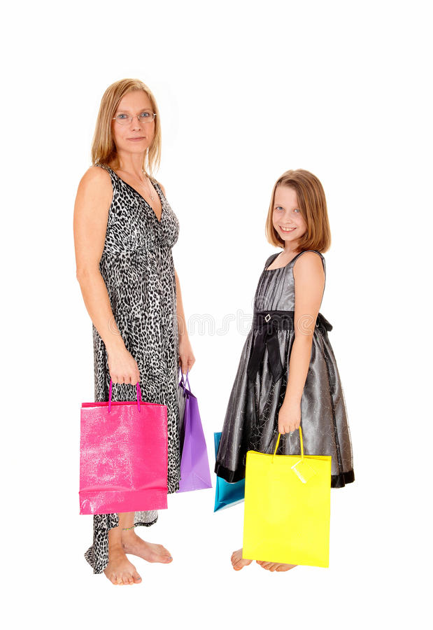 Mother and daughter shopping. A mother and her daughter standing isolated for white background with shopping bag's in there hands royalty free stock image