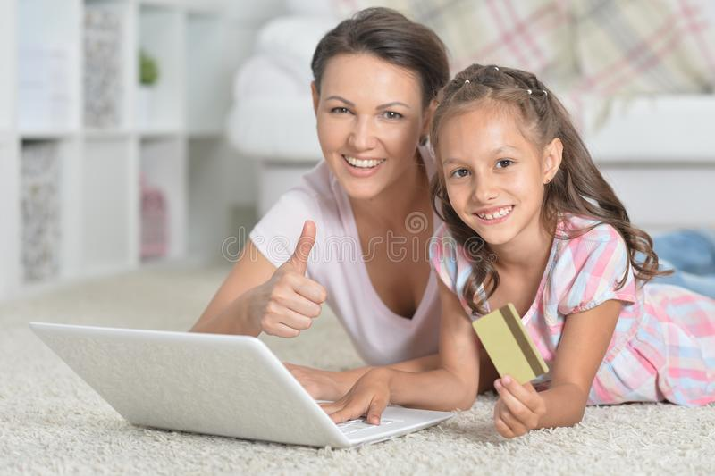 Portrait of mother and daughter shopping online while lying on floor. Mother and daughter shopping online while lying on floor royalty free stock photos